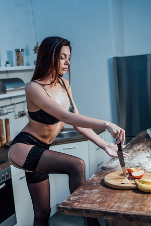 Sexy girl in black lingerie with knife in kitchen