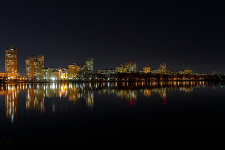 Malowniczy ciemny pejzaż miejski z oświetlonymi budynkami, rzeką i nocnym niebem