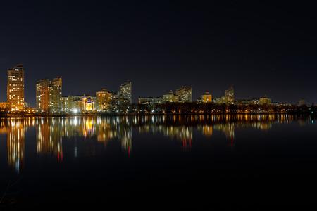 Pittoresco paesaggio urbano scuro con edifici illuminati, fiume e cielo notturno