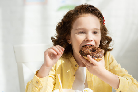 Adorable kid in yellow eating delicious doughnut at table