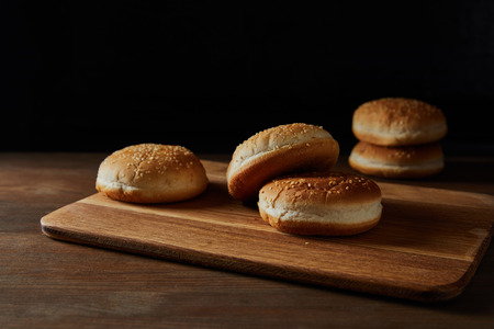 Tasty buns with sesame on wooden chopping board isolated on black background 版權商用圖片