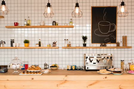 Interior of coffee shop with wooden bar counter, shelves and tiled wall Imagens - 120877769