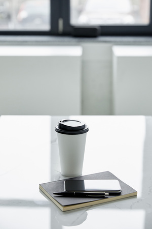 Smartphone with blank screen, notebook, pen and disposable cup on white table