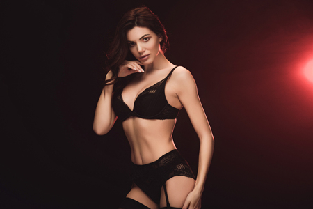 Bella donna seducente in lingerie di pizzo che guarda l'obbiettivo su nero con sfondo a luce rossa