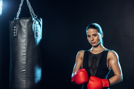Strong boxer in red gloves standing near punching bag and looking at camera on black