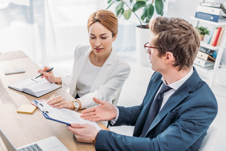 Overhead view of attractive hr looking at clipboard with document near coworker in glasses Imagens