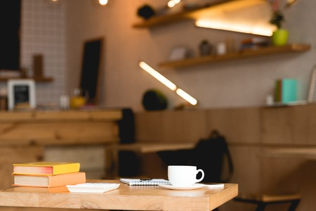 Selective focus of wooden table with books and coffee cup in cafeteria Stock Photo