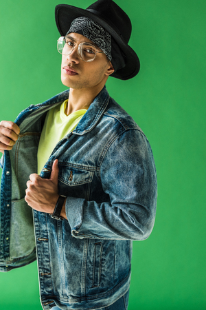 Stylish mixed race man in glasses posing and looking at camera on green screen background