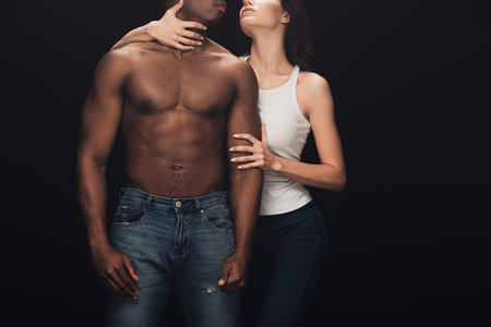 Cropped view of woman embracing shirtless African American man isolated on black background