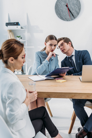 Selective focus of recruiters speaking near woman during job interview