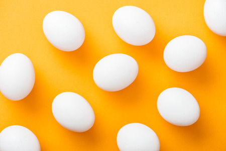 Top view of whole white fresh chicken eggs on bright orange background