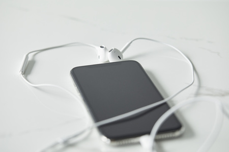 Selective focus of earphones connected to smartphone with blank screen on white surface