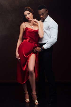 Beautiful sensual interracial couple in formal wear posing isolated on black background