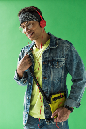 Handsome mixed race man in headphones listening music and smiling on green screen