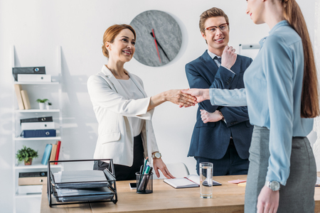 Cropped view of woman shaking hands with cheerful recruiter near handsome coworker in glasses
