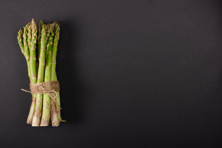 Top view of bunch of green uncooked asparagus tied with rope on black background