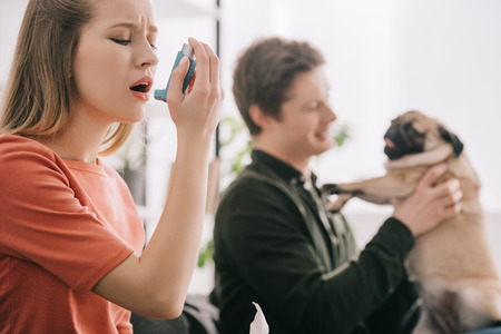 Selective focus of attractive blonde woman allergic to dog using inhaler near man with pug