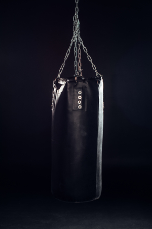 Leather punching bag hanging on steel chains on black background Stockfoto
