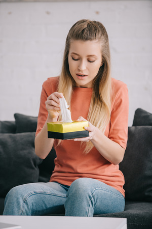Blonde woman holding tissue box while sitting on sofa at home