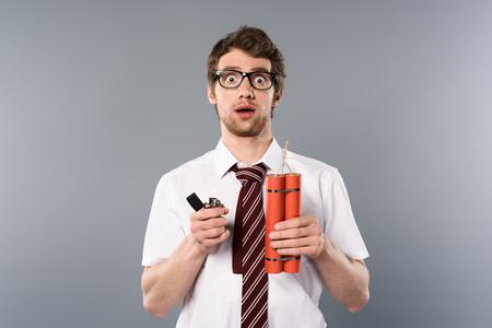 Shocked businessman holding lighter and dynamite on grey background