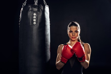 Front view of boxer in red boxing gloves standing near punching bag on black background