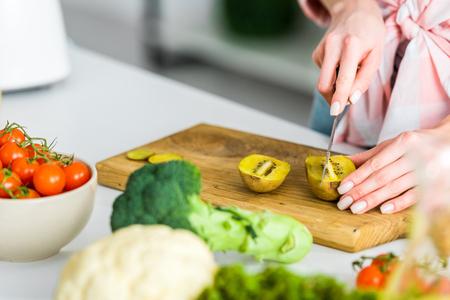 cropped view of girl cutting kiwi fruit near ingredients in kitchen