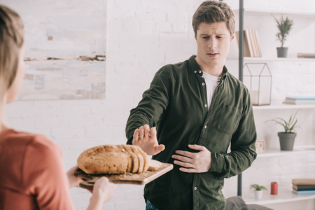 Cropped view of woman holding cutting board with sliced bread near handsome man with gluten allergy