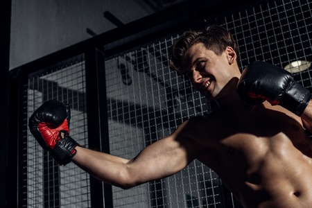 Handsome boxer in black boxing gloves training with smile Stok Fotoğraf - 121416124