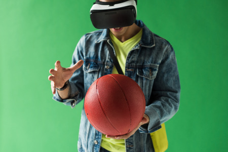 Mixed race man in virtual reality headset gesturing while holding basketball on green screen background