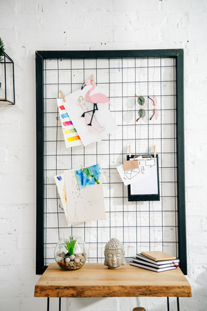 Pinboard with drawings and glasses and wooden table in teenage room