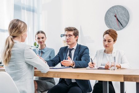 Handsome recruiter gesturing while looking at woman on job interview Imagens