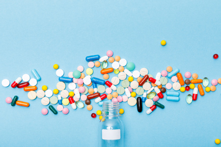 Top view of colorful pills on blue surface