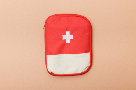Top view of red first aid kit bag on brown surface Banque d'images - 120878414