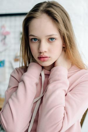 Tienerkind in casual roze hoodie die naar de camera kijkt