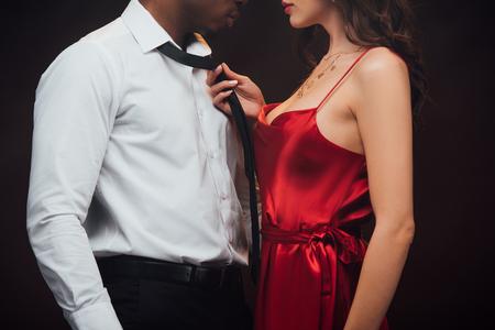 Vue recadrée d'une femme en robe rouge tenant une cravate d'un homme afro-américain isolé sur fond noir