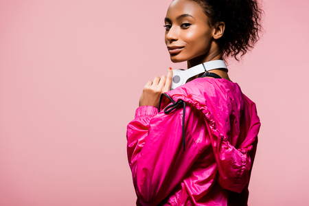 Beautiful African American sportswoman with headphones looking at camera isolated on pink with copy space Reklamní fotografie