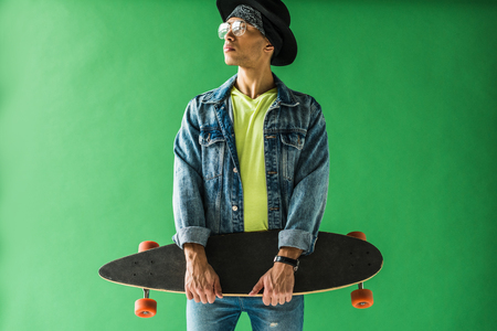Stylish mixed race man in denim posing with skateboard on green screen background