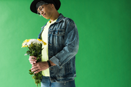 Stylish mixed race man in denim posing with flowers on green screen with copy space