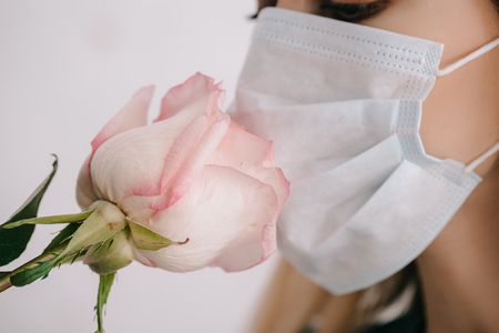 Cropped view of woman in medical mask smelling rose Stock Photo