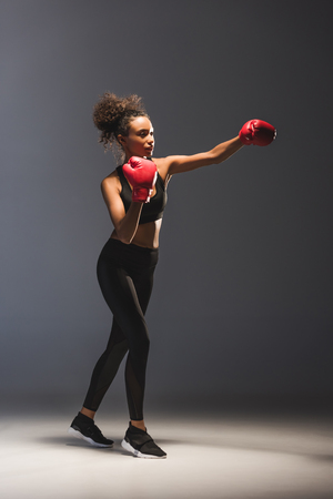 Beautiful athletic African American sportswoman boxing on black background