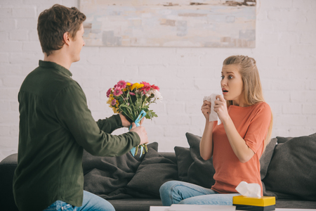 A man holding flowers near shocked woman with with pollen allergy Banco de Imagens