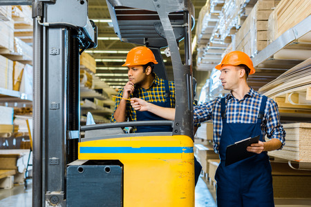 Indian warehouse worker sitting in forklift machine near colleague pointing with pencil Stockfoto