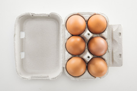 top view of raw brown chicken eggs in carton box on white background