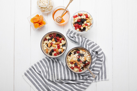 Top view of bowls with muesli, dried berries and nuts served for breakfast with dried apricots and honey near striped cloth on white wooden table Stock Photo