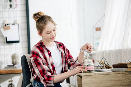 Adolescent en chemise à carreaux mettant de l'argent dans la tirelire
