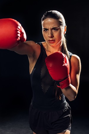 Focused female boxer in red boxing gloves training and looking away on black background 版權商用圖片