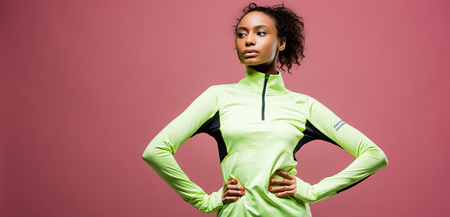 Panoramic shot of beautiful African American sportswoman in track jacket isolated on pink with copy space Stock Photo