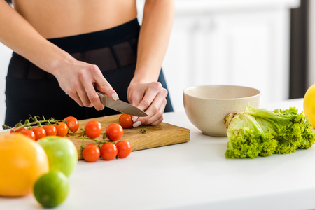 Cropped view of woman cutting red cherry tomatoes on cutting board Stok Fotoğraf