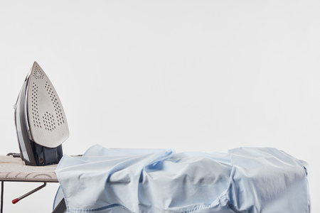 Iron and blue shirt on ironing board isolated on white