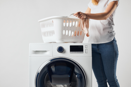 Partial view of woman with landry basket and washing machine isolated on grey Standard-Bild - 120973669